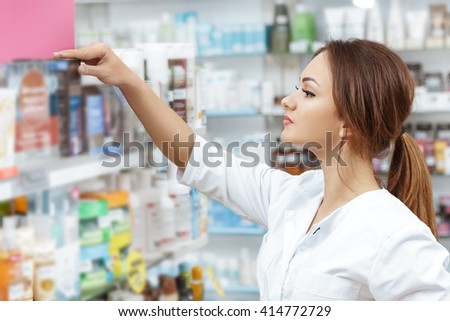 Perfect placement. Professional pharmacist checking medical products on the drugstore shelf carefully. - stock photo