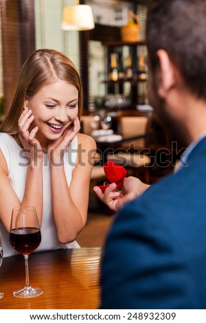 Perfect proposal. Rear view of handsome young man making a proposal while giving an engagement ring to his girlfriend in restaurant  - stock photo