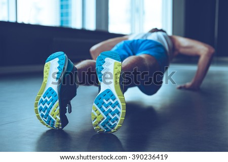 Perfect push-up. Rear view of young man in sportswear doing push-up at gym - stock photo