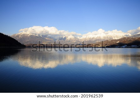 Perfect reflections of snowy mountains in a blue lake  - stock photo