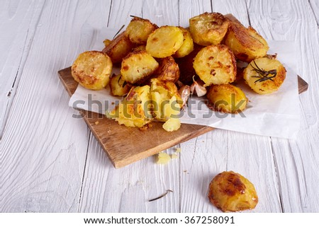 Perfect roasted potatoes with spices and herbs on wood board - stock photo