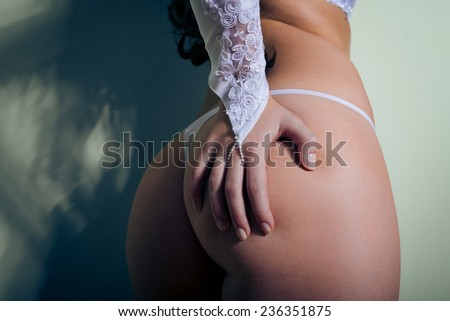 Perfect sexy buttocks of pretty woman in white lingerie with hand on bum close-up picture  - stock photo
