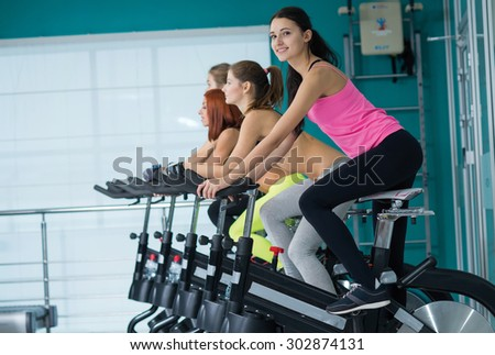 Perfect shape and ideal workout. Young and pretty woman is having training on exercise bike. Her friends are also on exercise bikes are next to her. Active workout in a gym. Healthy sportsmen concept - stock photo
