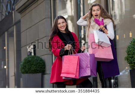 Perfect shopping. Two young pretty stylish girls are holding the shopping bags and looking forward in a good mood. Happy shopping with smiles. Road to mall dress shops. Ideal shopping. Festive sales