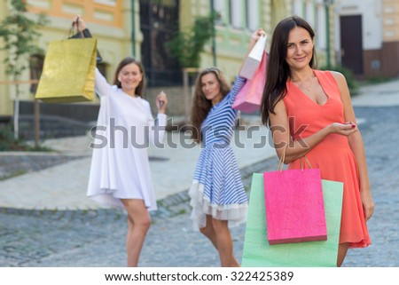 Perfect shopping with a smile. Portrait of  young and pretty girl holding the shopping bags and looking forward in a good mood. Happy shopping with smiles. Mall and sales