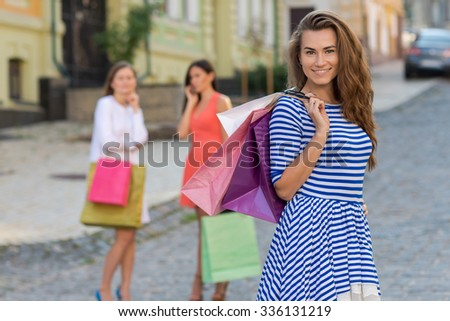 Perfect shopping with a smile. Portrait of  young pretty stylish girl holding the shopping bags and looking forward in a good mood. Ideal shopping. Mall sales and dress shop
