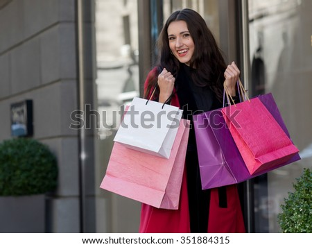 Perfect shopping with a smile. Portrait of  young pretty stylish girl holding the shopping bags and looking forward in a good mood. Ideal shopping. Mall sales and festive dress shop - stock photo