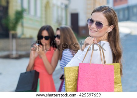 Perfect shopping with a smile. Portrait of  young pretty stylish girl holding the shopping bags and looking forward in a good mood. Ideal shopping. Mall sales and festive dress shop