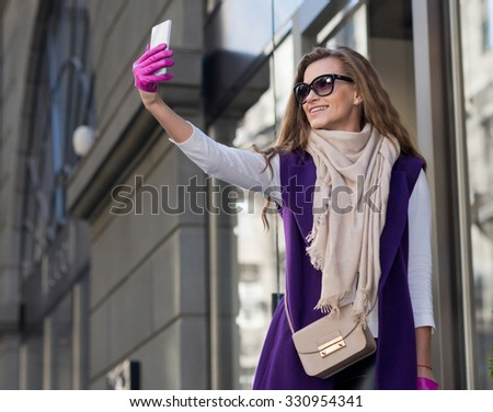 Perfect shopping with a smile. Young pretty and stylish girl is holding the shopping bags and making selfie on a sell phone. Happy shopping with smiles. Mall and sales concept