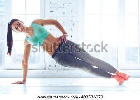 Perfect side plank. Full length of young beautiful woman in sportswear doing side plank and looking at camera in front of window at gym  - stock photo