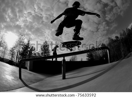 perfect silhouette of a skateboarder doing a flip trick at the skate park. - stock photo