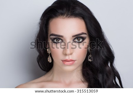 Perfect smoky eyes, professional make-up. Horizontal photo, free grey space for text. Portrait of black-haired girl with thick curly hair, best model agency, makeup studio visage master. fashion trend - stock photo