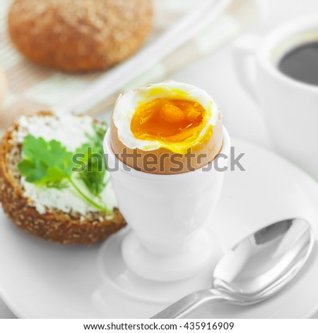 Perfect soft boiled egg, open bread sandwich with butter and cup of coffee on a table. Traditional food for healthy breakfast.