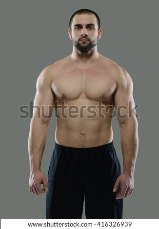 Perfect sport shape in a gym. Portrait of young and handsome man having training in a gym on pure grey background. Active workout. Healthy sportsmen fitness concept - stock photo