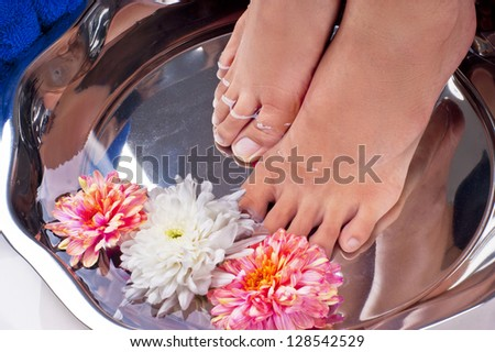 perfect stunning cute feet enjoying the most relaxing foot spa filled with luke warm water and beautiful flowers in preparation for a amazing pedicure - stock photo