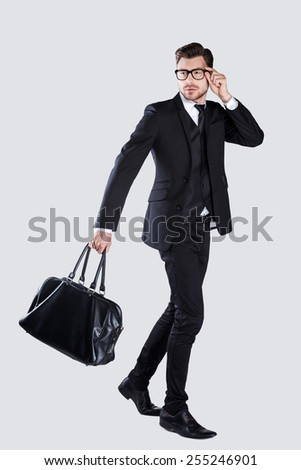 Perfect style. Full length of confident young man in formalwear and eyeglasses carrying briefcase while walking against grey background  - stock photo