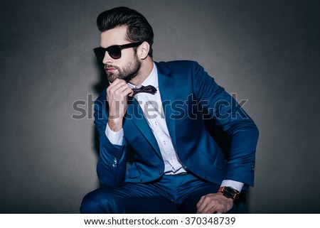 Perfect style. Young handsome man in suit and bow tie holding hand on chin and looking away while sitting against grey background - stock photo