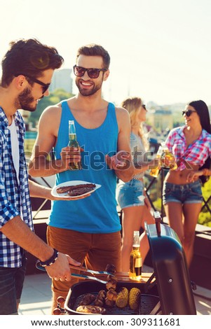 Perfect summer lunch. Two cheerful young men barbecuing and smiling while two women talking to each other in the background  - stock photo