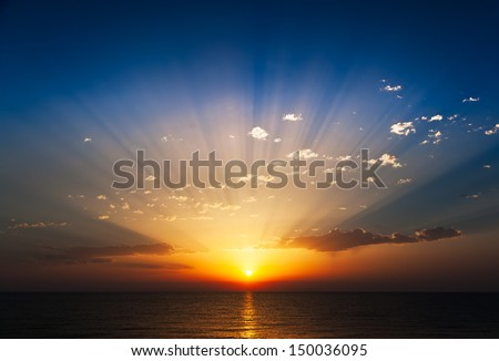 Perfect sunrise on the sea, with radiant rays of sun over a warm colourful horizont. - stock photo