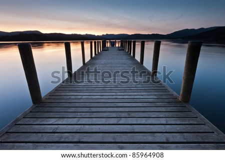 Perfect symmetry, a wooden jetty on Lake Windermere one tranquil autumn morning with the Langdales in the background - stock photo