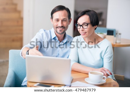Perfect team. Smiling and merry businesspeople using laptop and communicating