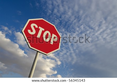 perfect texture of the surface of a stop sign against blue sky and white clouds - stock photo