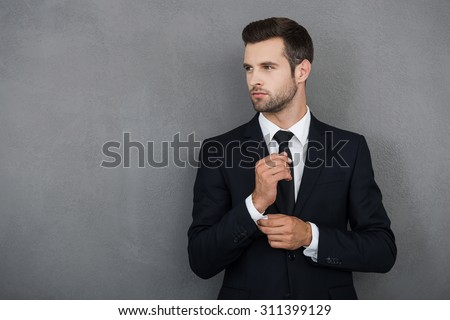 Perfect to the last detail. Handsome young businessman adjusting his sleeves while standing against grey background - stock photo
