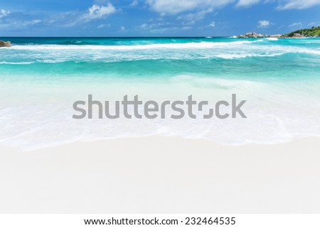 Perfect tropical beach Anse Cocos in La Digue, Seychelles with granite boulders and palm trees