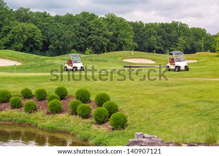 Perfect wavy ground with nice green grass on a golf field  with golf carts - stock photo