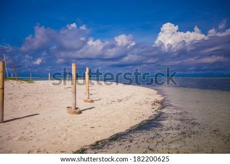 Perfect white beach with turquoise water and a small fence on desert island