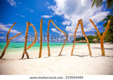 Perfect white sandy beach and turquoise sea on tropical island with wooden letters made Friday word - stock photo