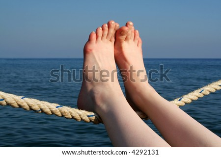 perfect woman feet laying on sail rope