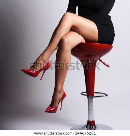 Perfect woman legs wearing high red heels with black evening dress sitting on red chair gray background - stock photo