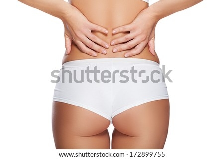 Perfect women body in white underwear and white shirt isolated on white, with hands on her back. Back ache concept  - stock photo