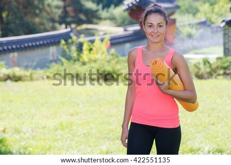 Perfect yoga workout. Beautiful young girl is preparing for doing yoga. Yoga outdoor class workout