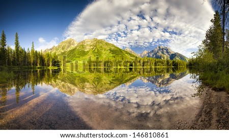 Perfectly calm water with brilliant reflections on String Lake in Grand Teton National Park, WY - stock photo