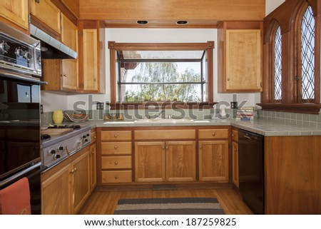 Perfectly fitted kitchen in craftsman home with bay window, lights, built in appliances, wooden panels and unique church like custom made view windows. - stock photo