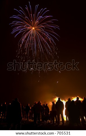 Perfectly framed blue firework starburst with audience silhouetted against bonfire. - stock photo