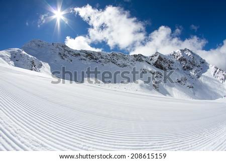 perfectly groomed empty ski piste, ski resort - stock photo