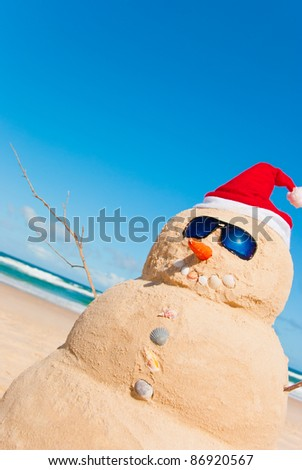 Perfectly Shaped Snowman made from sand whit santa hat and sunnies. There is loads of copy space for text in the sky - stock photo