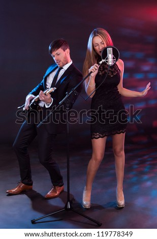 Performers entertain audience through musical instruments and songs. - stock photo