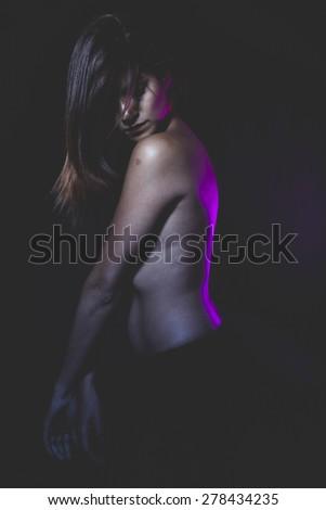 Performing, latina naked ballerina in a black tutu and pink light - stock photo