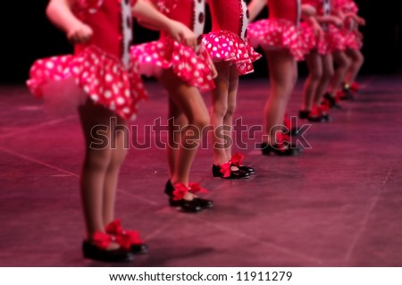 Performing on stage, a group of young dancers show off their talent and bright costumes - image highlights a narrow depth of field on the girl in the middle of the line - stock photo