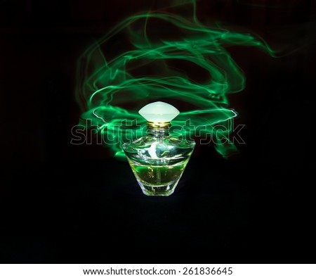Perfume bottle and green light painting on the black background - stock photo