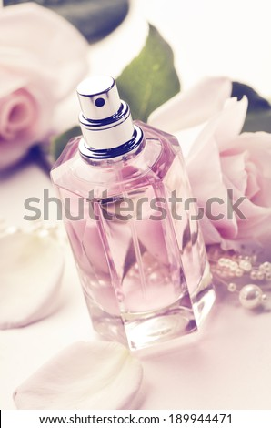 Perfume bottle and roses. Retro style. - stock photo