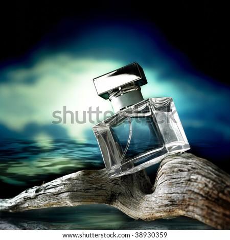 Perfume bottle on wood at sunset - stock photo