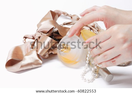 Perfume bottle with female accessories and pearl bracelet - stock photo