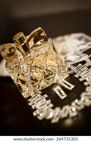 Perfume bottle with necklace and earrings on the black background - stock photo