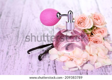 Perfume bottle with roses petals on table close-up - stock photo