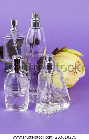 Perfume Bottles on violet background - stock photo